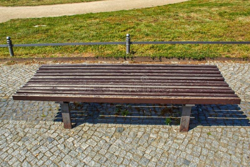 Широкомасштабная коричневая деревянная скамейка в парке стоковые изображения