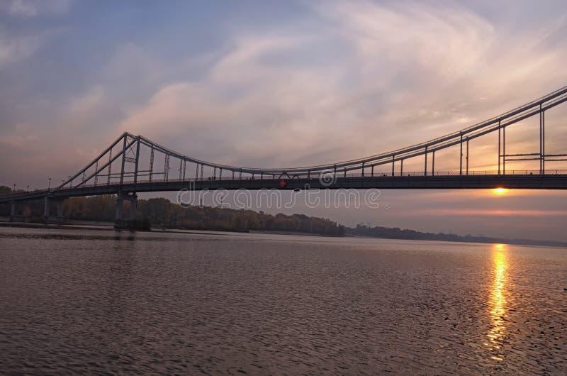 Широкоформатная панорама ландшафта реки Dnipro, обваловки и пешеходного моста Красочное живое небо, солнце отраженное в воде стоковые фото