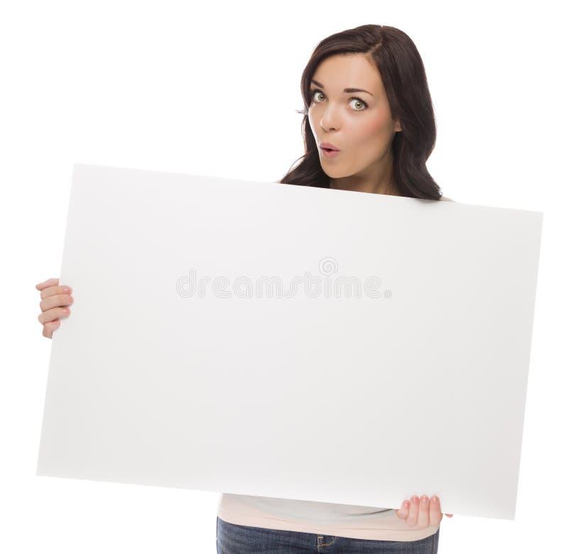 Широко наблюданная женщина смешанной гонки держа пустой знак на белизне стоковое изображение