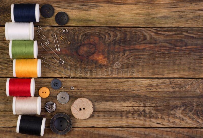 Шить аксессуары на деревянной предпосылке стоковая фотография rf