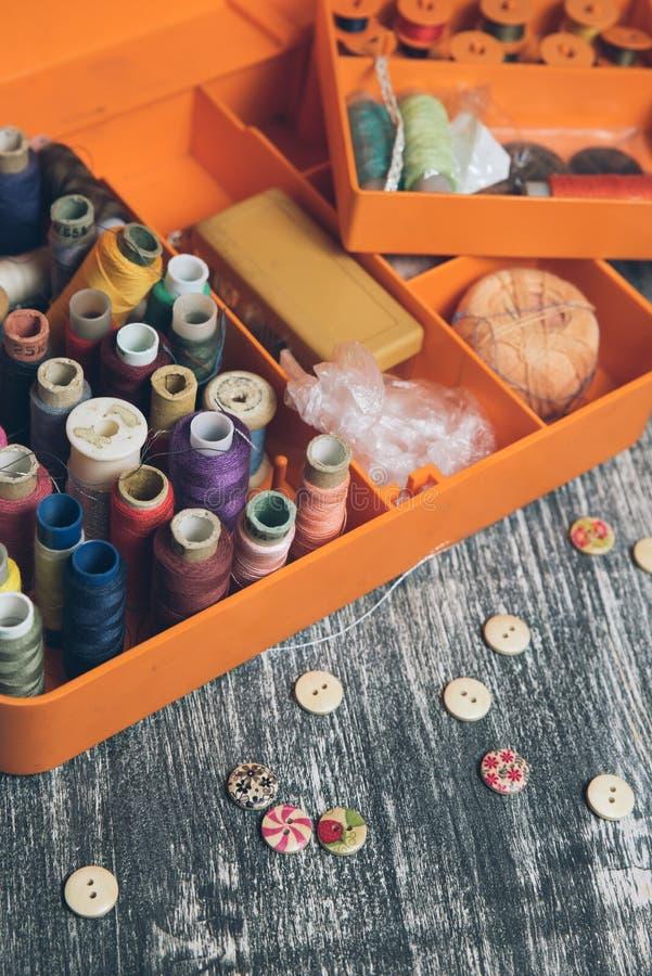 Шить инструменты и аксессуары на оранжевом ларце стоковое фото
