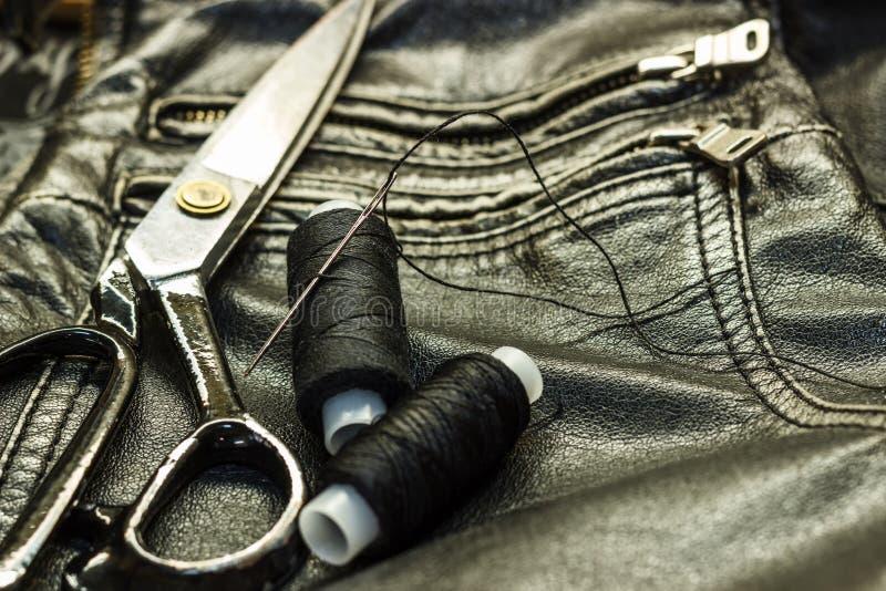 Шить кожаная куртка, ремонт ножниц кожаной куртки, поток, конец-вверх Продукты кожи стоковые фото