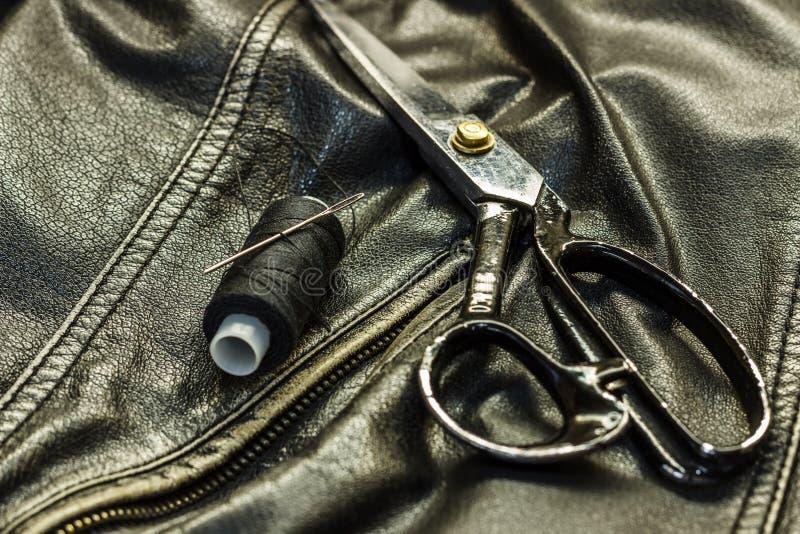 Шить кожаная куртка, ремонт ножниц кожаной куртки, поток, конец-вверх Продукты кожи стоковые изображения rf