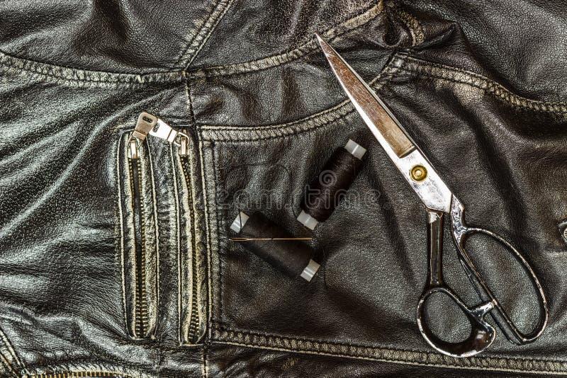 Шить кожаная куртка, ремонт ножниц кожаной куртки, поток, конец-вверх Продукты кожи стоковое изображение