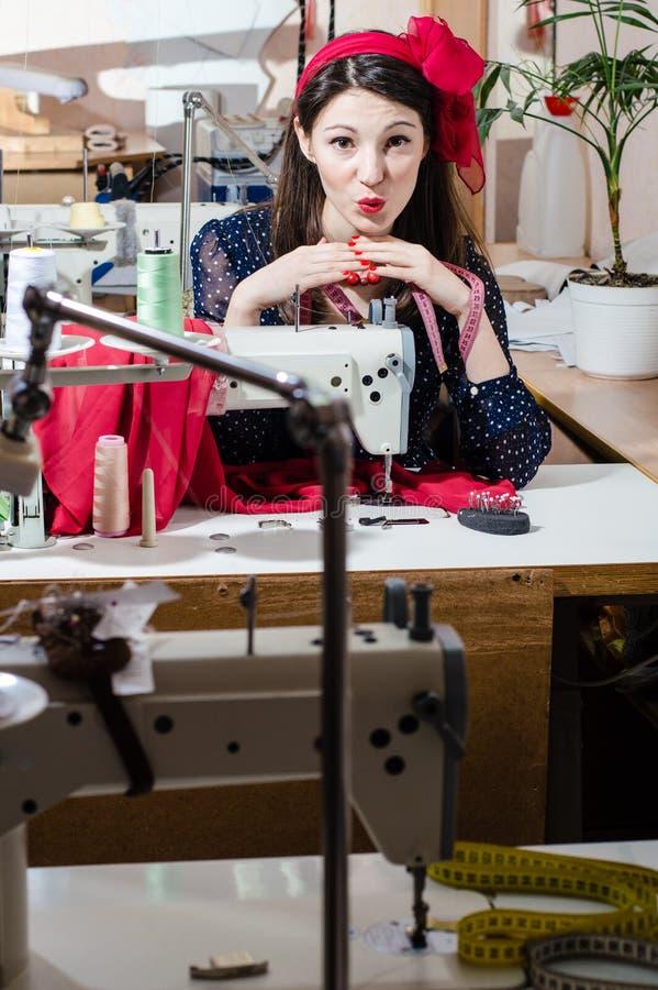 Шить одевает в молодой женщине брюнет мастерской красивой с лентой на ее голове стоковые изображения rf