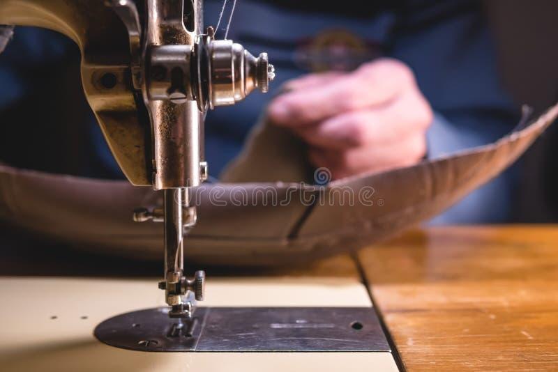Шить процесс кожаного пояса руки старика за шить Кожаная мастерская шить ткани винтажный промышленный стоковые изображения