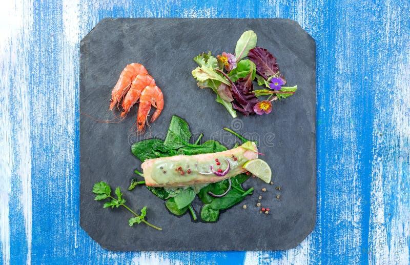 Шифер подготовленный с испаренными семгами, салатом и креветкой на сини стоковое изображение rf