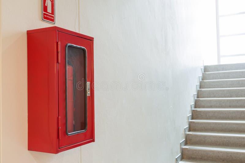Шкаф огнетушителя на белой стене около лестницы стоковое изображение
