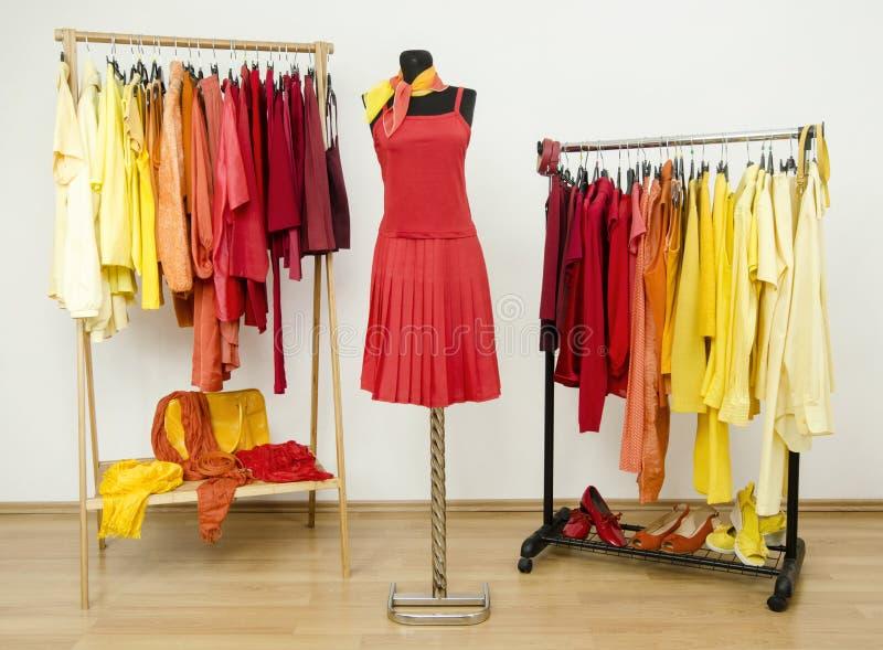 Шкаф с желтыми, оранжевыми и красными одеждами аранжировал на вешалках и красном обмундировании на манекене стоковые изображения rf