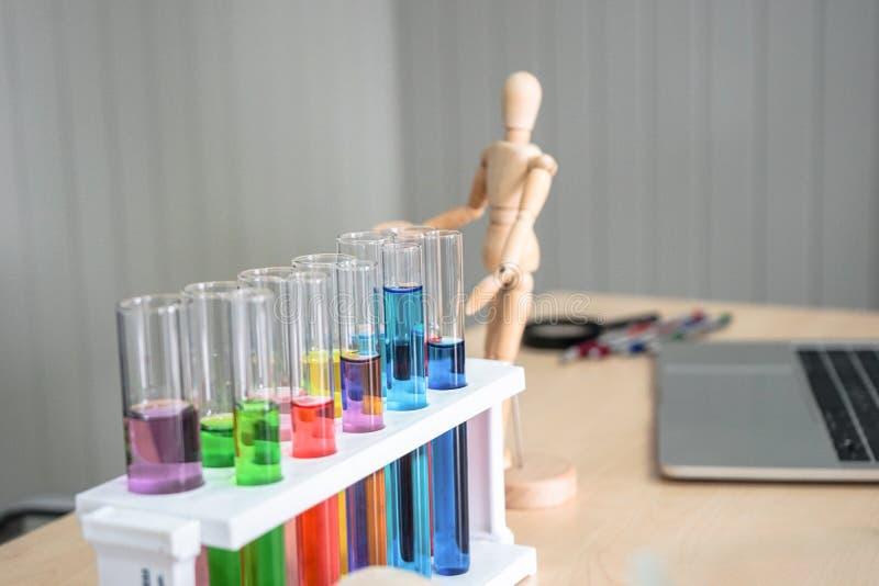 Шкаф с пробирками, стеклоизделие лаборатории, с красочными химическими жидкостями на таблице с чистой белой предпосылкой Химическ стоковое фото rf