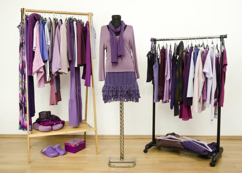 Шкаф с фиолетовыми одеждами аранжировал на вешалках и обмундировании на манекене стоковые фото
