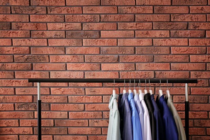 Шкаф шкафа со стильными одеждами около кирпичной стены стоковое фото