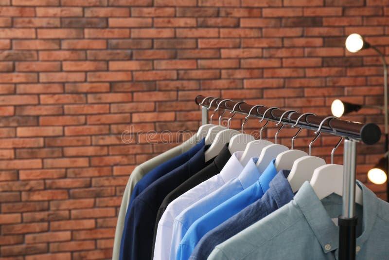 Шкаф шкафа со стильными одеждами около кирпичной стены стоковое изображение rf