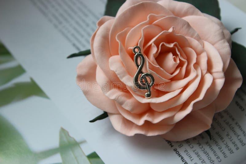 Шкентель в форме дискантового ключа на предпосылке розового цветка стоковые изображения