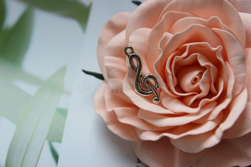 Шкентель в форме дискантового ключа на предпосылке розового цветка стоковые изображения rf