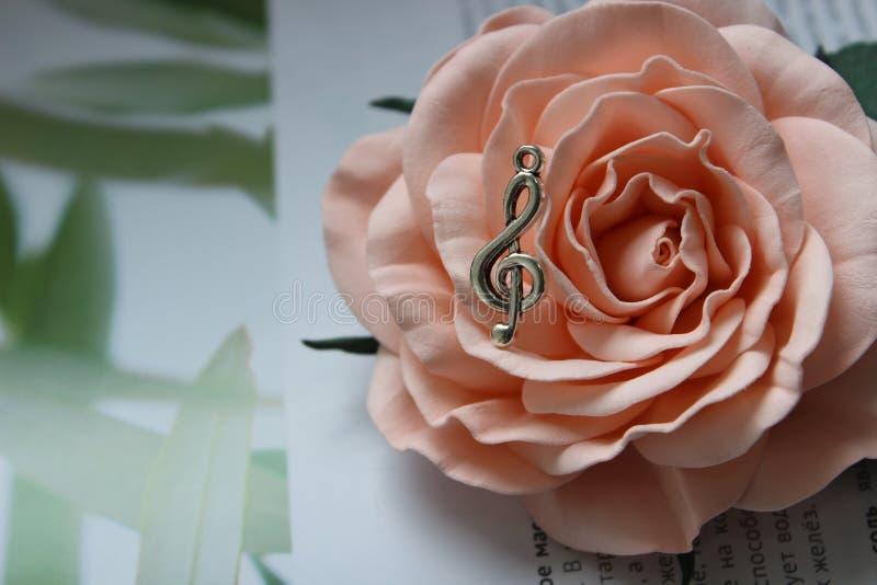 Шкентель в форме дискантового ключа на предпосылке розового цветка стоковое изображение
