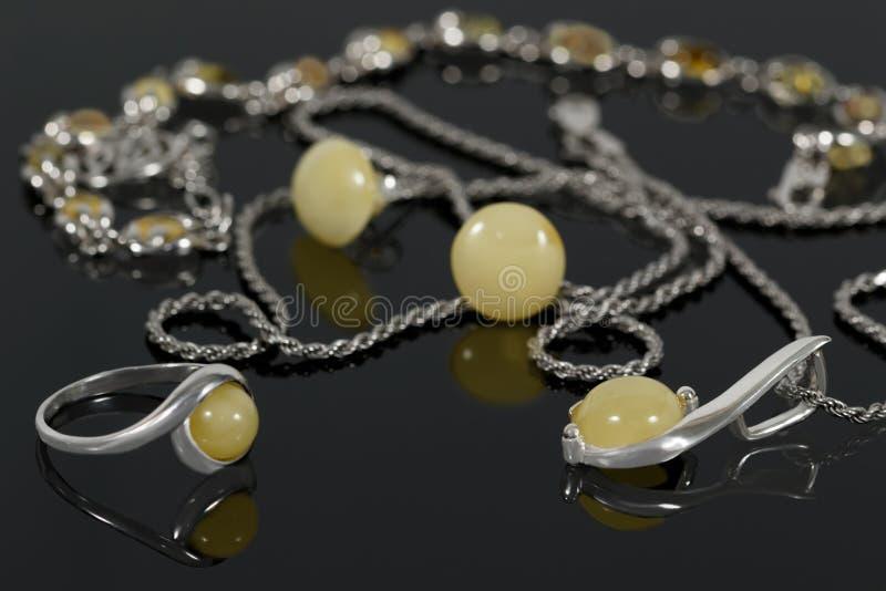 Шкентель и кольцо крупного плана серебряные на серьгах и браслете предпосылки на черном акриловом столе стоковые изображения