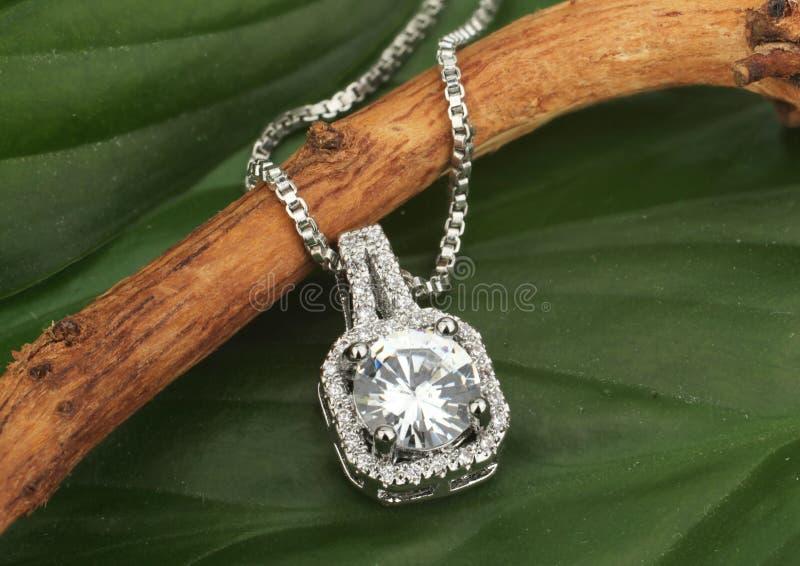 Шкентель ювелирных изделий с большими диамантами, на зеленых листьях  стоковое изображение