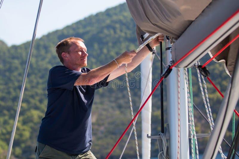 Шкипер затягивает веревочки на его яхте плавания Спорт стоковые изображения rf