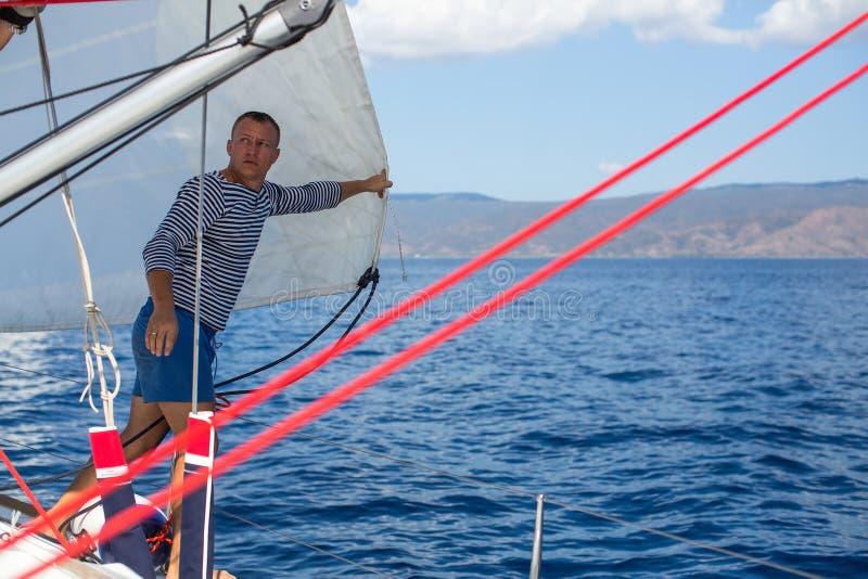 Шкипер молодого человека - ветрила установки на плавании плавать шлюпка стоковое изображение