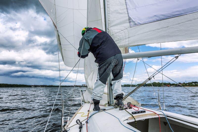 Шкипер устанавливает ветрило на небольшие спорт плавает на яхте на море стоковые фото