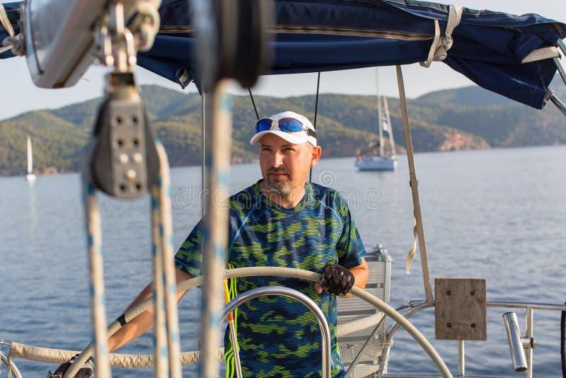 Шкипер у руля его яхты плавания Спорт стоковая фотография