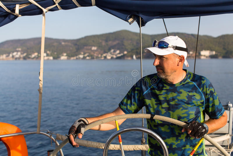Шкипер человека во время в состязания по гребле яхт стоковые изображения rf