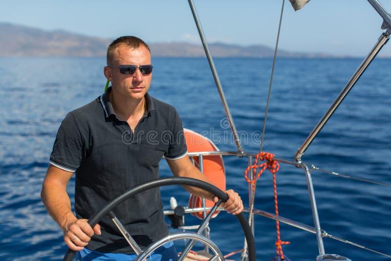 Шкипер человека управляет парусником на море стоковое изображение rf