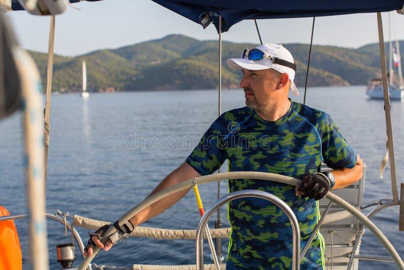 Шкипер человека управляет парусником на море стоковые фотографии rf
