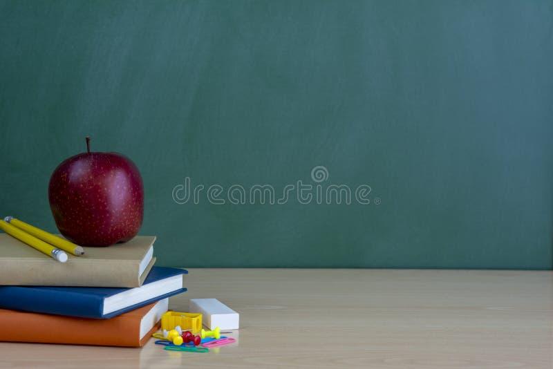 Школа и канцелярские товары на таблице класса перед blackb стоковое изображение
