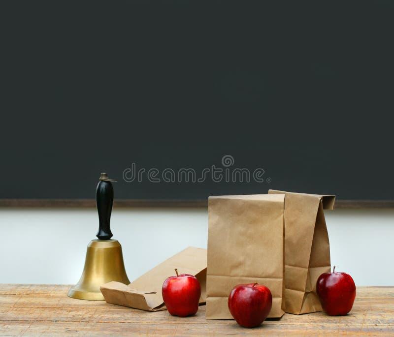 школа обеда стола колокола мешков яблок стоковые фотографии rf
