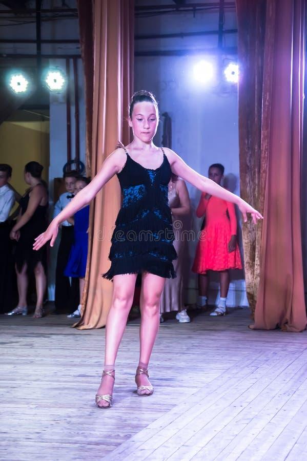 Школа танцев Зрачки принимают экзамены Мальчики и девушки в красивых костюмах танца на этапе стоковые фото