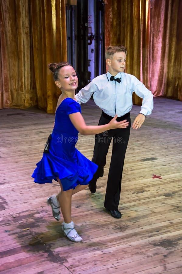 Школа танцев Зрачки принимают экзамены Мальчики и девушки в красивых костюмах танца на этапе стоковое фото