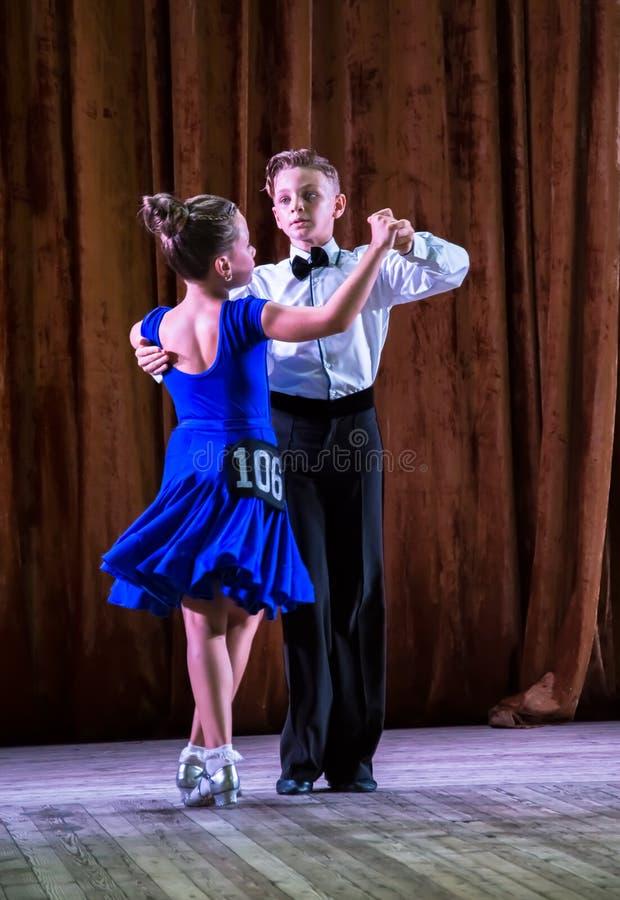 Школа танцев Зрачки принимают экзамены Мальчики и девушки в красивых костюмах танца на этапе стоковые изображения rf