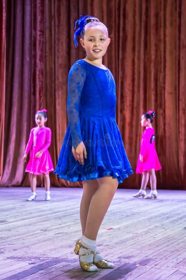 Школа танцев Зрачки принимают экзамены Мальчики и девушки в красивых костюмах танца на этапе стоковая фотография rf