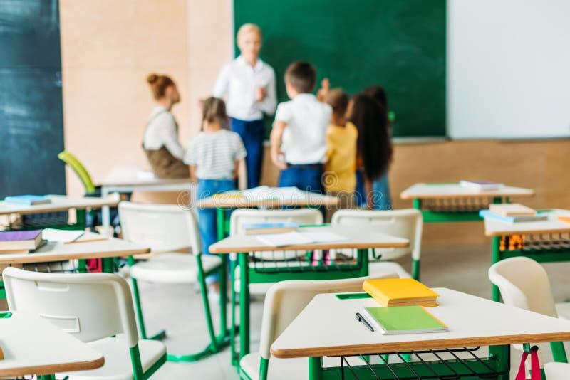 школьники стоя вокруг учителя на классе со столами стоковые фотографии rf