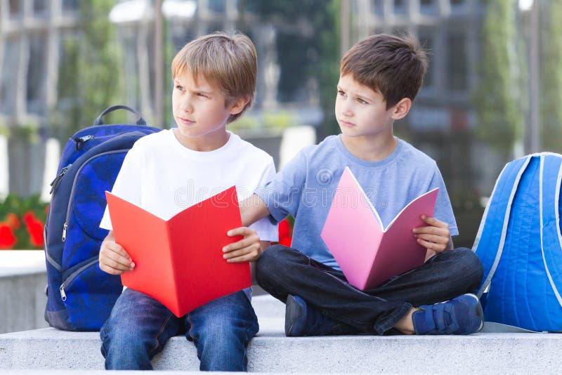 Школьники уча чтение, делая домашнюю работу после школы outdoors стоковая фотография rf