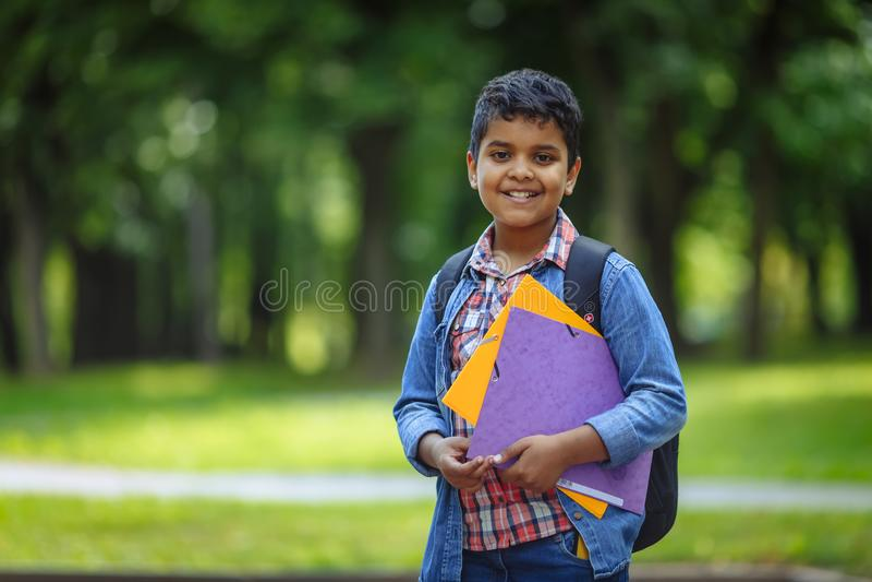 Школьник на открытом воздухе американца портрета афро счастливый с книгами и рюкзаком Молодое начало студента класса после канику стоковая фотография rf