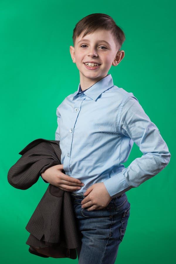 Школьник представляя на зеленой предпосылке стоковые фото