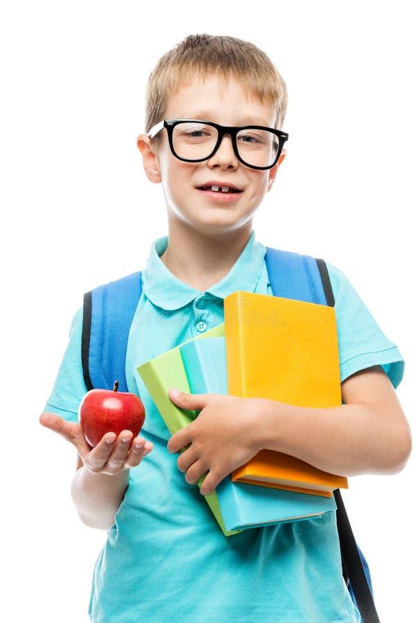 школьник при книги показывая красное яблоко для обеда на белизне стоковое изображение rf