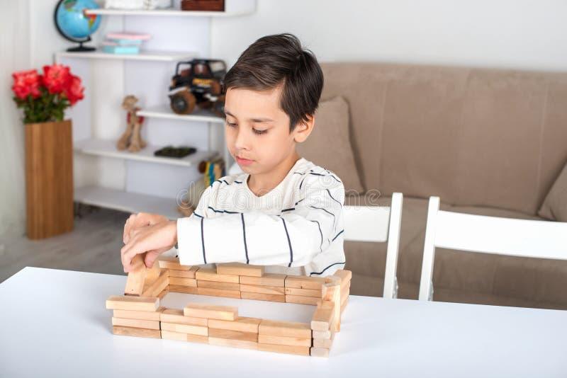 Школьник сидит на таблице и играх в деревянные жулики стоковое фото