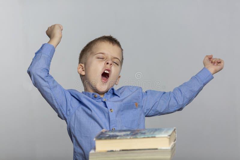 Школьник сидит на таблице с книгами, зевками и глоточками Предпосылка серого цвета стоковая фотография rf
