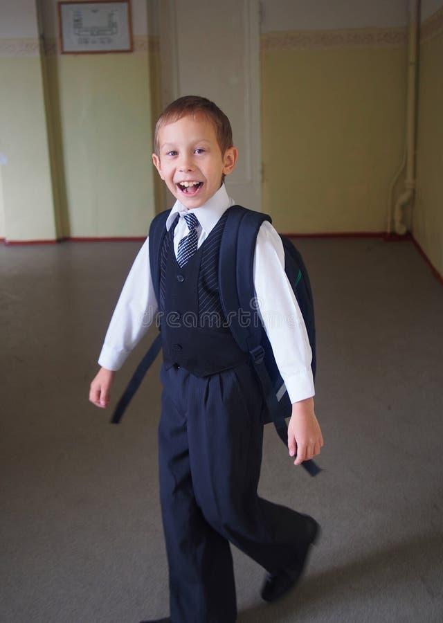 Школьник с рюкзаком плача в школе стоковая фотография