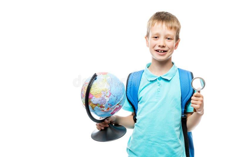 Школьник с увеличителем и глобусом в руках представляя на белизне стоковые изображения rf