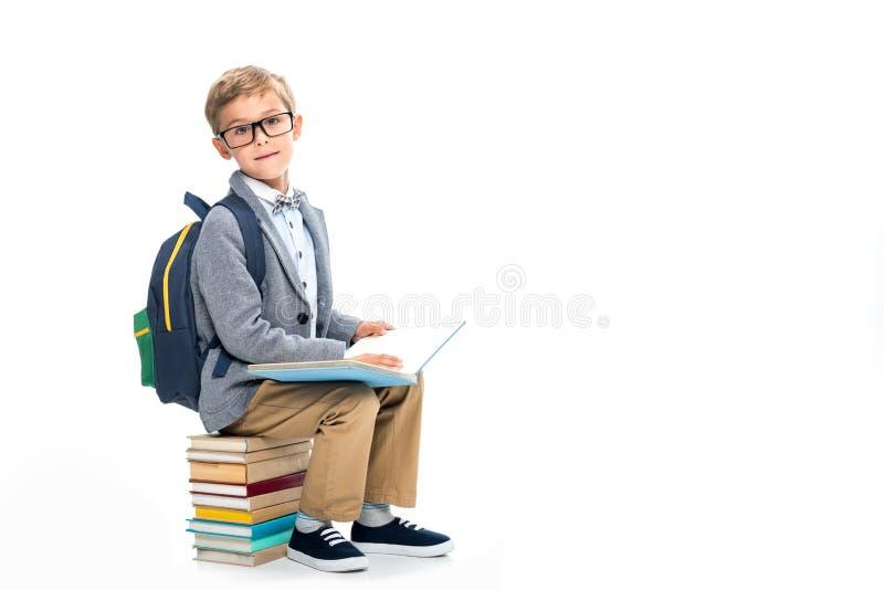 Школьник sittting на стоге книг и читать стоковые изображения