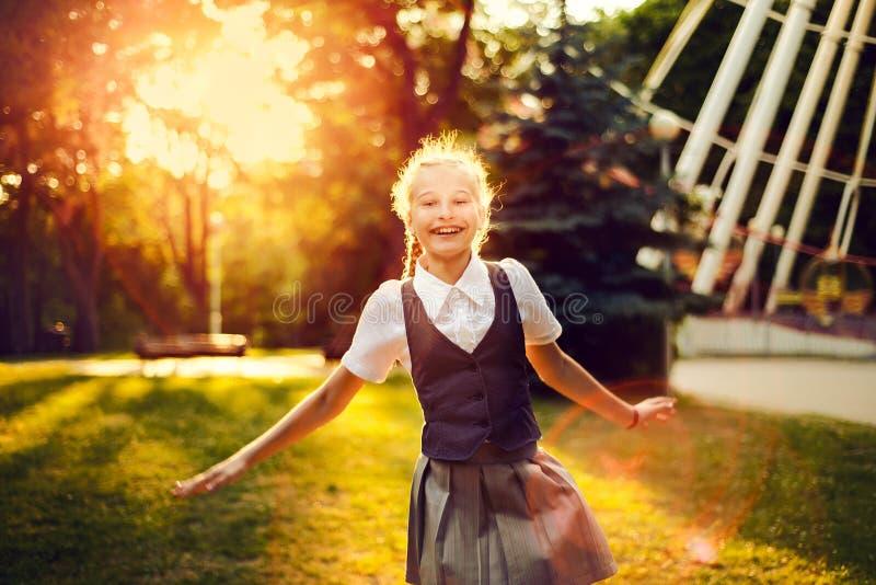 Школьница в форме с танцами отрезков провода радостными на заходе солнца i стоковые изображения