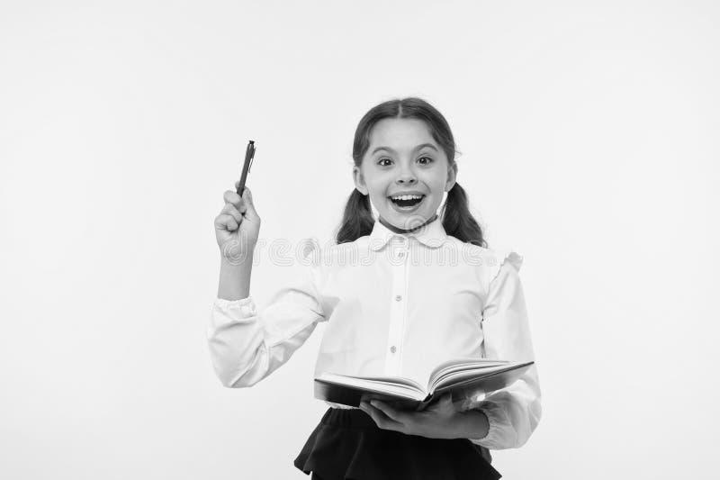 Школьница девушки милая в равномерной предпосылке книги или учебника владением желтой Старательно зрачок получает знание от книги стоковое изображение