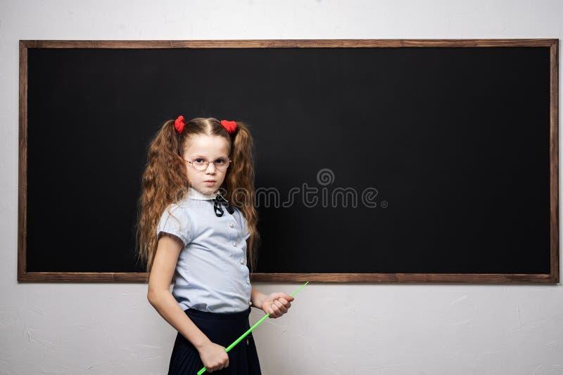 Школьница девушки стоит на школьном правлении и держит указатель стоковые изображения rf