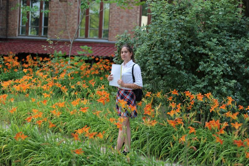 Школьница девушки с папкой в его руках стоковые изображения