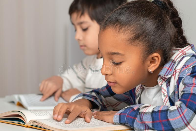 Школьница и школьник распологая на таблицу внутри помещения и делая их домашнюю работу стоковое изображение rf